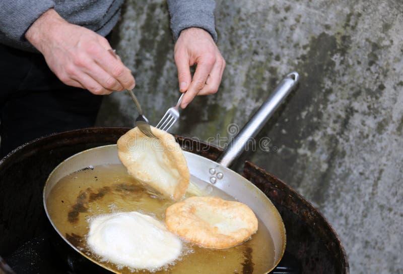 Mains pendant la préparation des beignets en huile chaude image stock