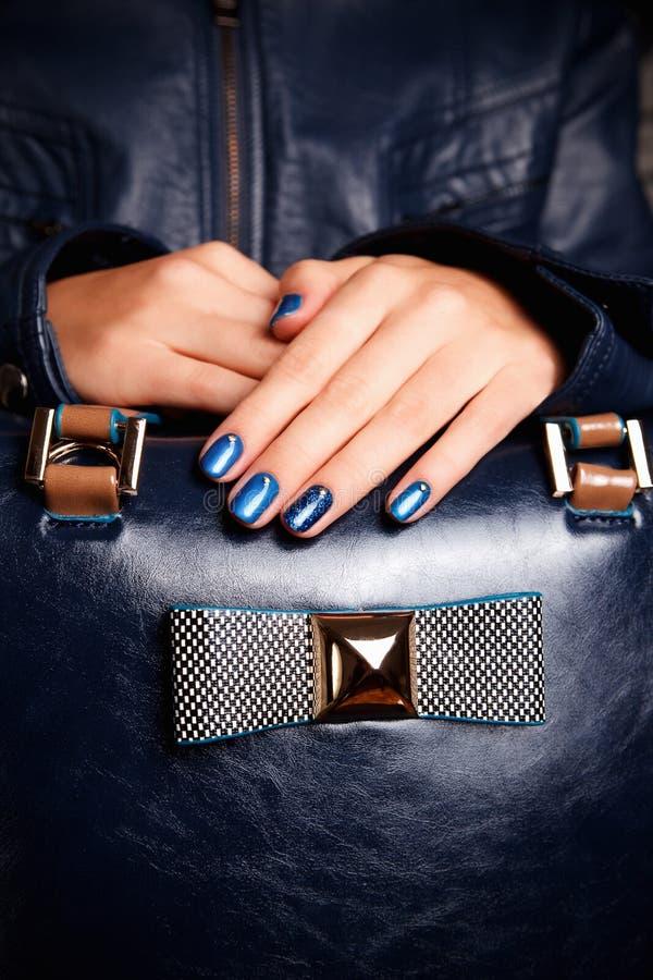 Mains polies par ongle exagéré sur un sac photographie stock