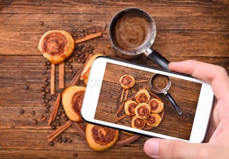 Mains prenant des petits pains de cannelle de photo avec le smartphone photographie stock libre de droits