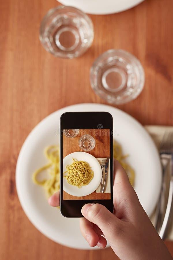 Mains prenant la photo du déjeuner avec le smartphone photo stock