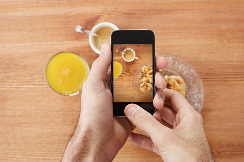 Mains prenant la photo du petit déjeuner avec le smartphone photo libre de droits