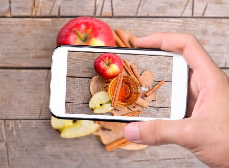 Mains prenant le cidre de photo avec le smartphone photographie stock