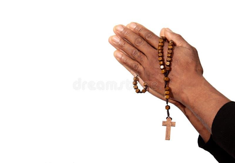 Mains priant avec la croix de perle de chapelet photo stock