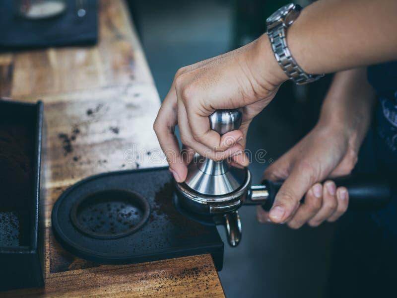 Mains professionnelles de barman pressant des marcs de café avec le bourreur en café photos stock