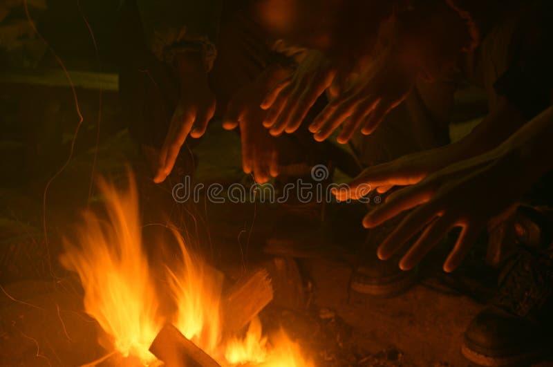 Mains réchauffant au-dessus d'un incendie en bois photographie stock