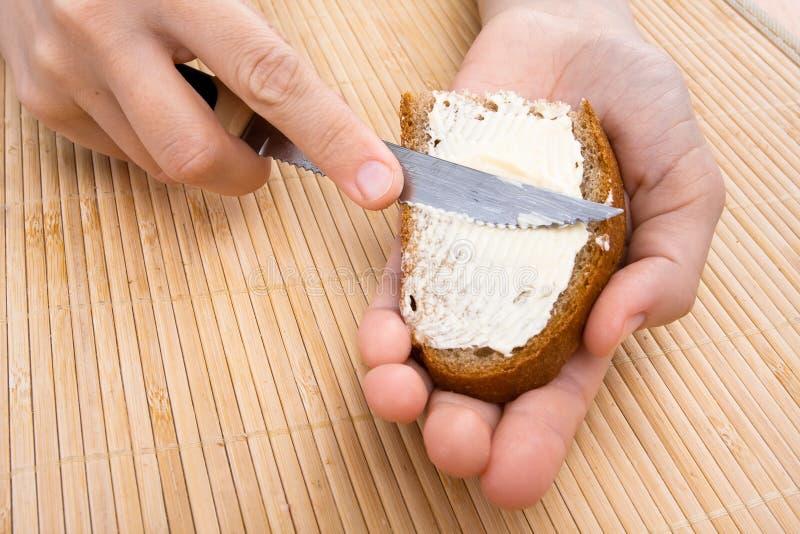 Mains répandant le beurre sur le morceau de pain image stock