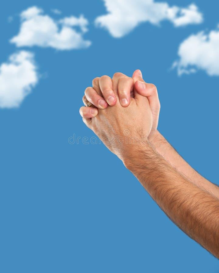 Mains remontées dans la position de prière images stock