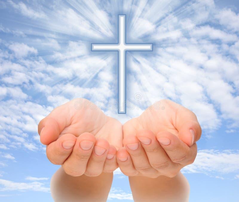 Mains retenant la croix chrétienne avec les faisceaux de lumière photographie stock