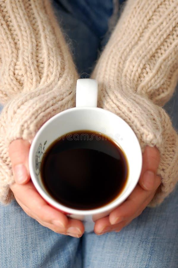 Mains retenant la cuvette de café foncé images libres de droits