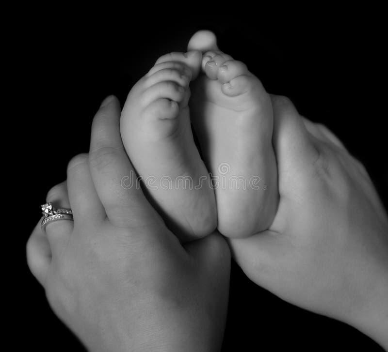 Mains retenant les pieds infantiles en noir et blanc images libres de droits