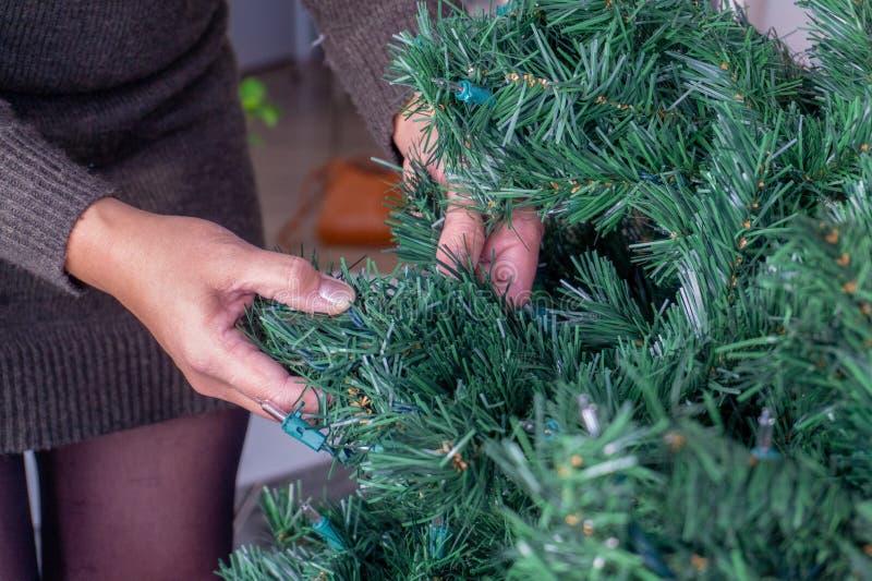 Mains se démêlant un faux arbre de Noël images stock