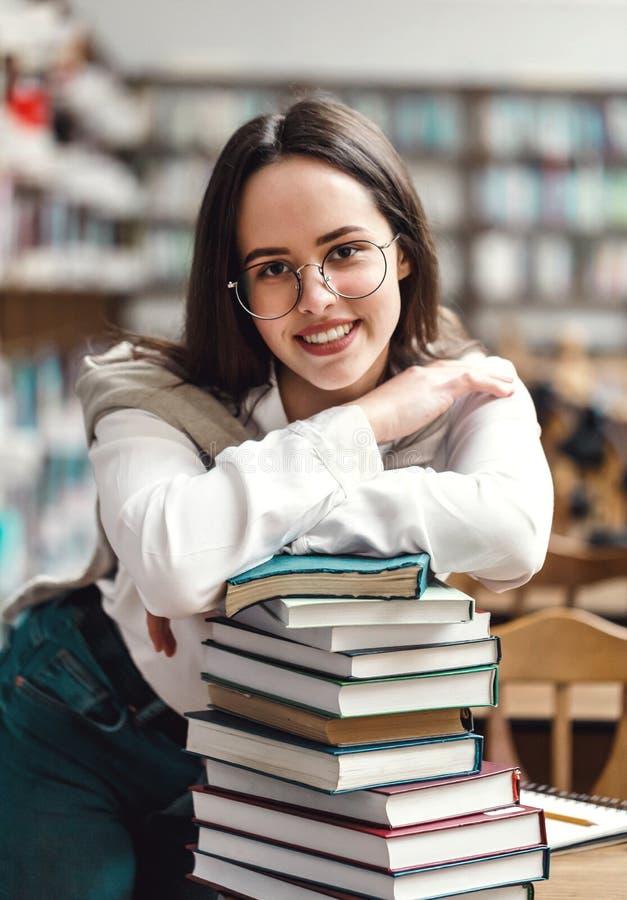 Mains se pliantes de fille sur les livres photo libre de droits