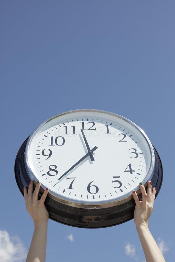 Mains soulevant la grande horloge à l'extérieur images stock
