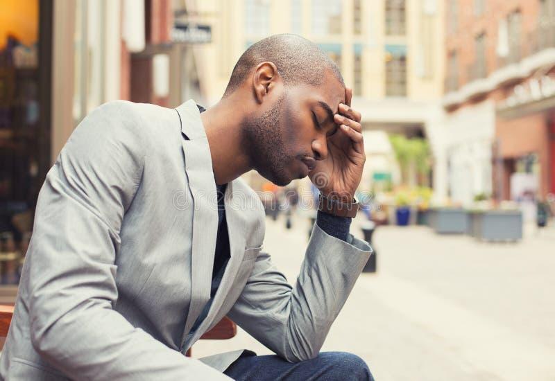 Mains soumises à une contrainte de jeune homme sur la tête avec le mauvais mal de tête photos stock