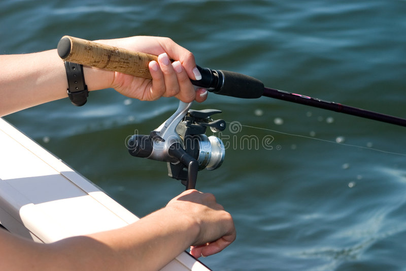 Mains sur la bobine de pêche photos stock