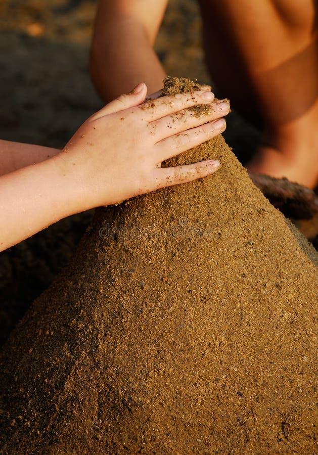 Mains sur le château de sable photo libre de droits