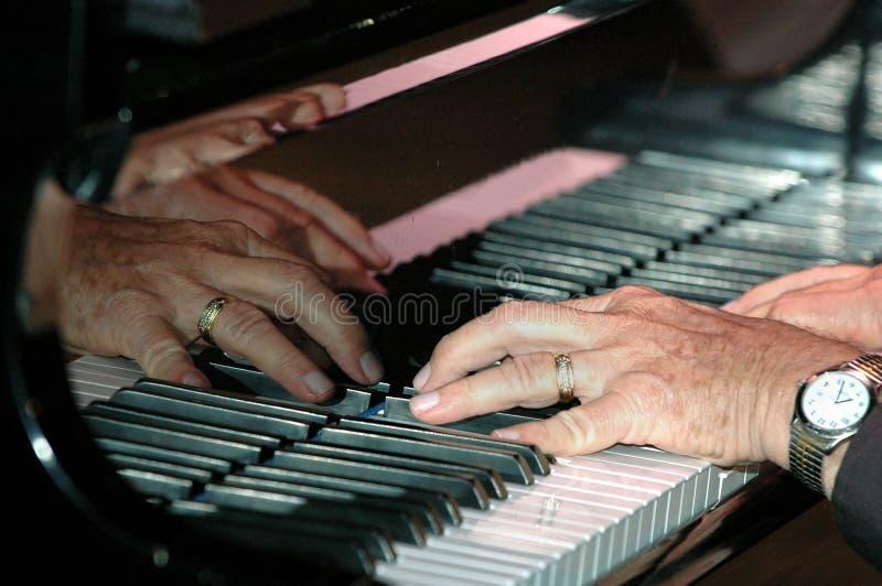 Mains sur le piano photos stock