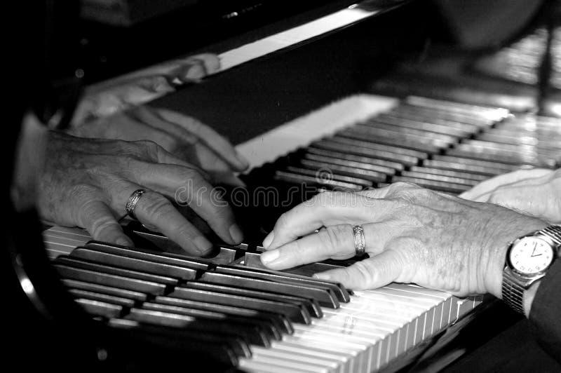 Mains sur le piano image stock