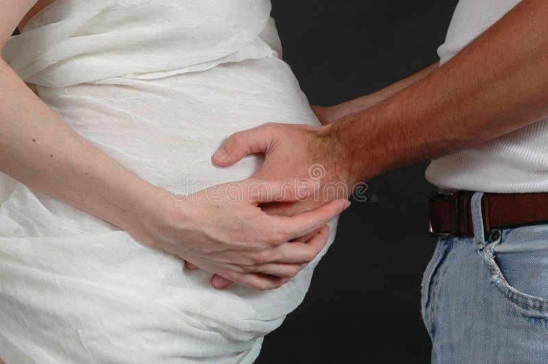 Mains sur le ventre images stock