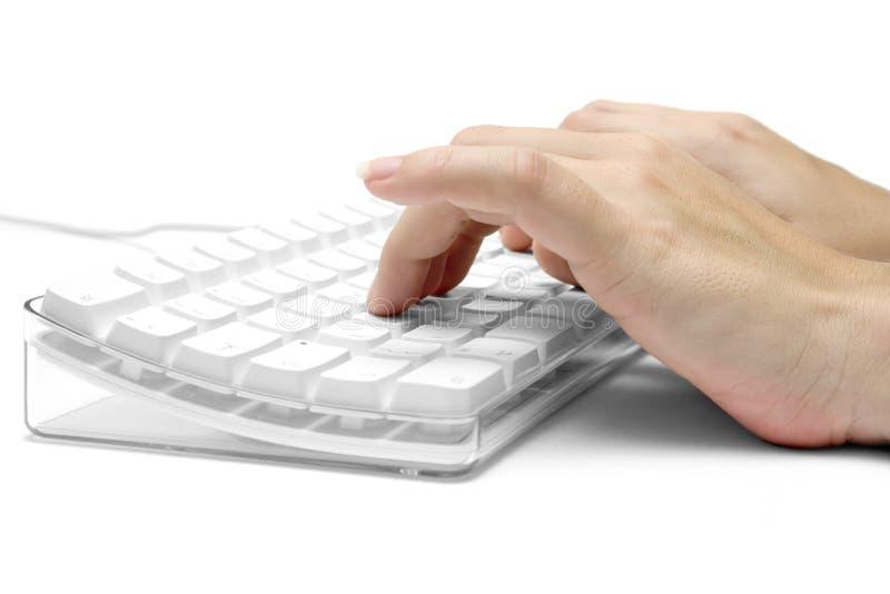 Mains sur un clavier d'ordinateur blanc photos stock