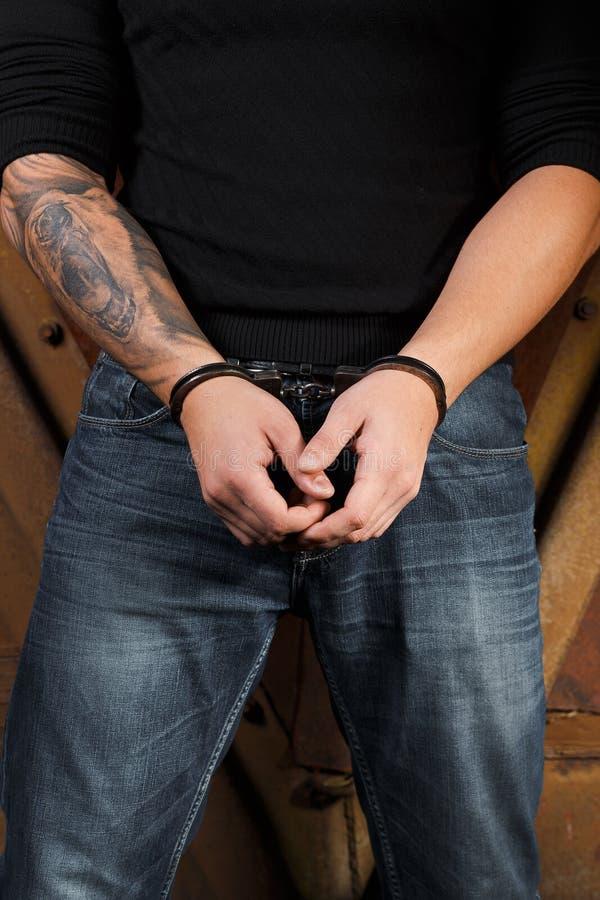Mains tatouées d'un criminel menotté photo stock