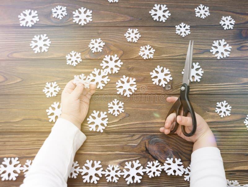 Mains tenant des ciseaux flocons de neige de coupe sur un fond en bois photographie stock