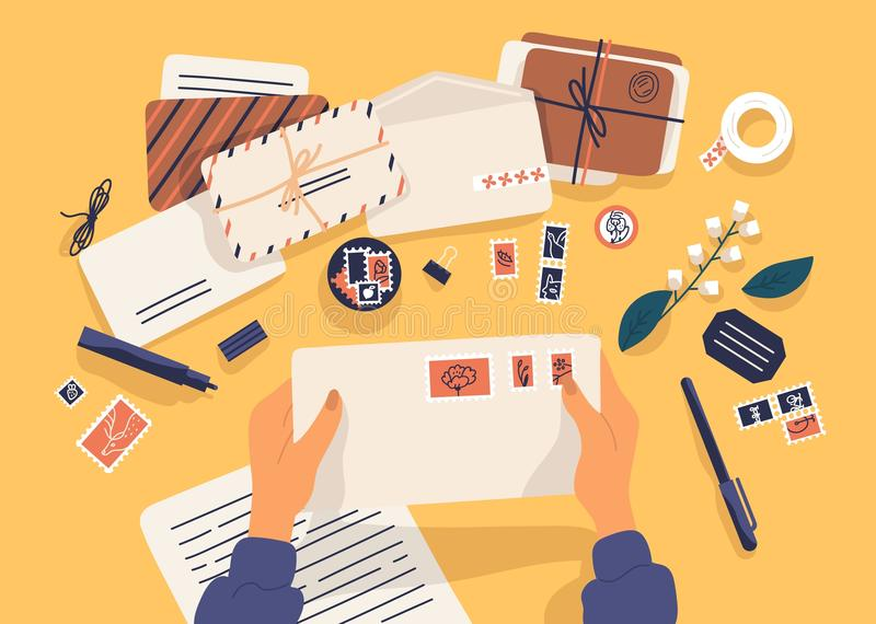 Mains tenant l'enveloppe avec des timbres entourés par des papiers, cartes postales, stylo sur le fond jaune Vue supérieure postc illustration stock