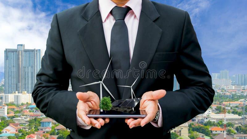 Mains tenant l'homme d'affaires sur une turbine de vent propre d'énergie électrique d'arbre de smartphone et une pile solaire l'a photos stock