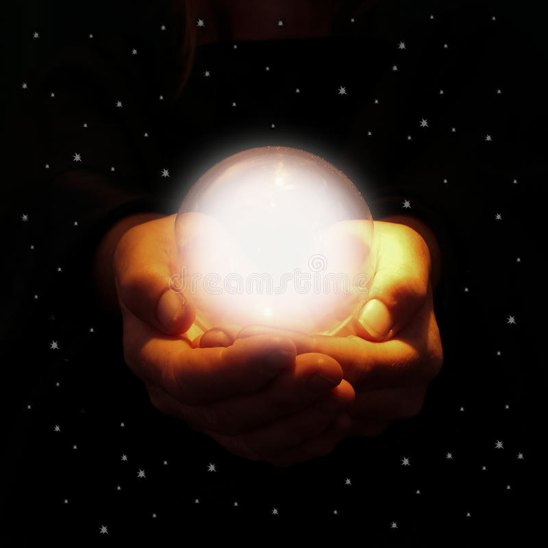 Mains tenant la boule de cristal rougeoyante photo stock