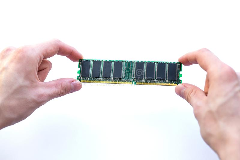 Mains tenant la carte de mémoire de RAM sur un fond blanc photos stock