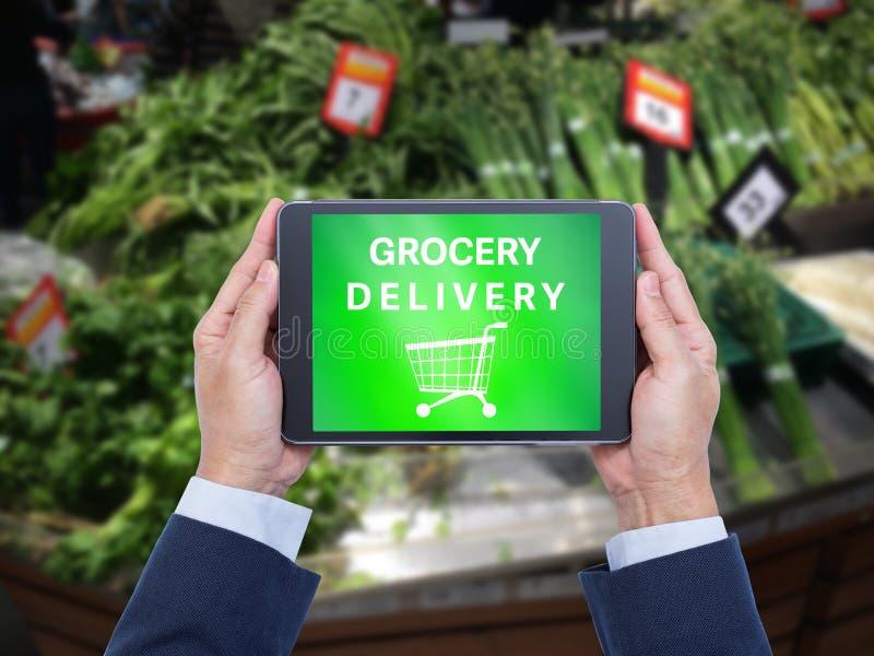 Mains tenant la tablette avec le mot de la livraison d'épicerie images stock