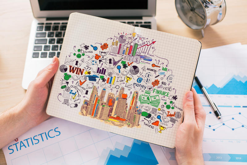 Mains tenant le bloc-notes avec le croquis d'affaires photos libres de droits