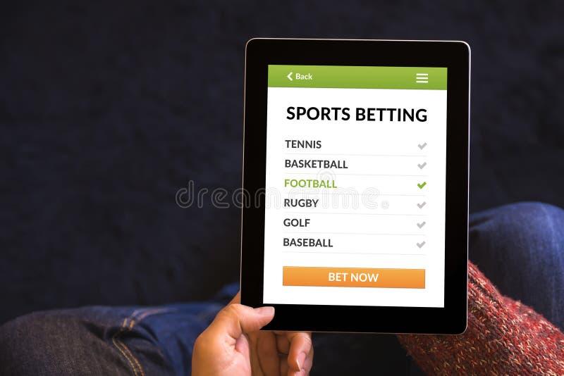 Mains tenant le comprimé avec des sports pariant le concept sur l'écran image stock