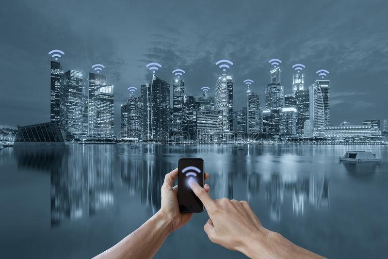 Mains tenant le concept de réseau de wifi de smartphone et de paysage urbain photo libre de droits