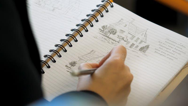 Mains tenant le crayon pour écrire ou dessiner dans un carnet Coloration adulte avec les crayons mous d'astuce Dessin femelle de  images stock