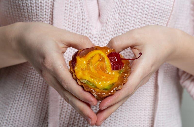 Mains tenant le petit gâteau délicieux avec des baies et orange femelles et faisant la forme de coeur photo libre de droits