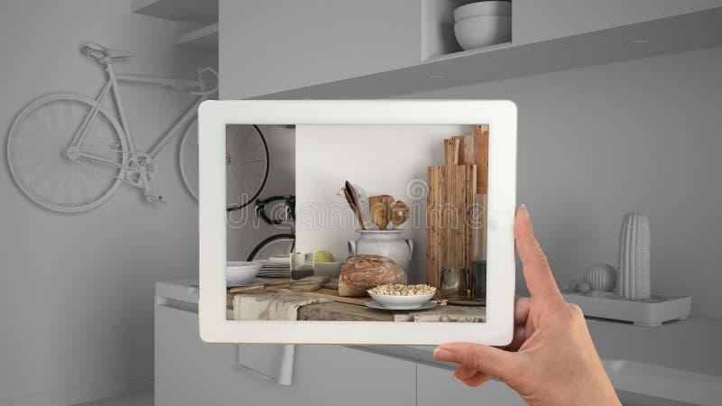 Mains tenant le plan rapproché moderne de cuisine d'apparence de comprimé Ébauche blanche totale de cuisine minimaliste à l'arriè image libre de droits