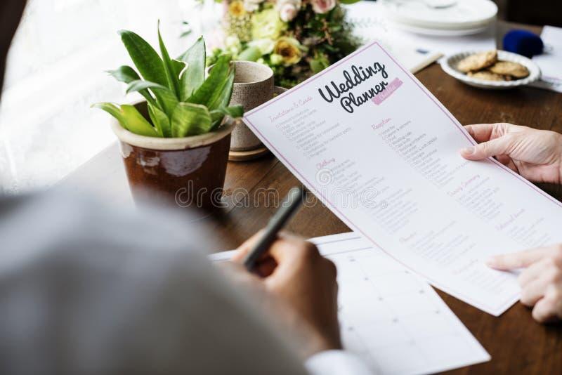 Mains tenant le planificateur Checklist Information Preparation de mariage photo stock