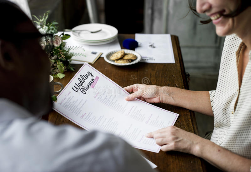 Mains tenant le planificateur Checklist Information Preparation de mariage photographie stock libre de droits