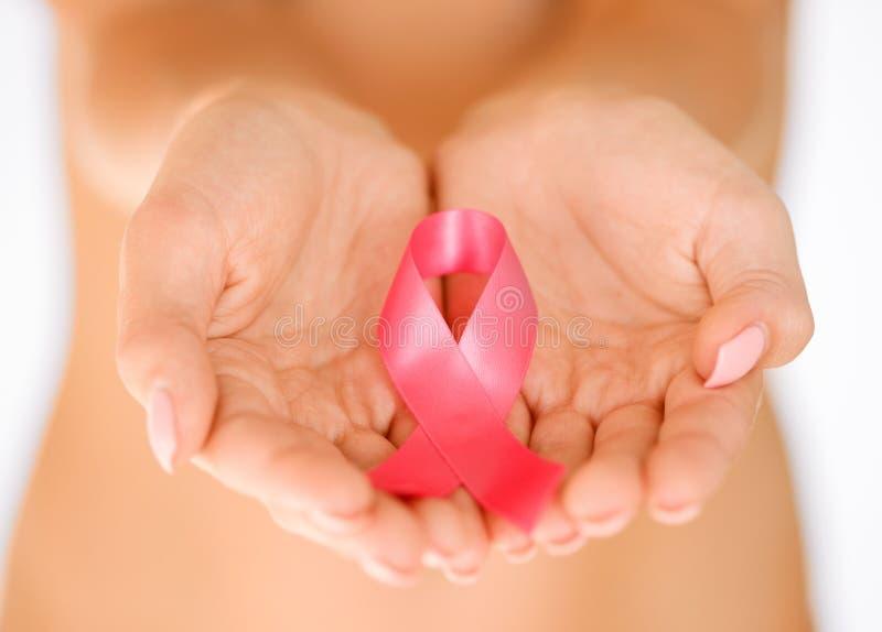 Mains tenant le ruban rose de conscience de cancer du sein photo stock
