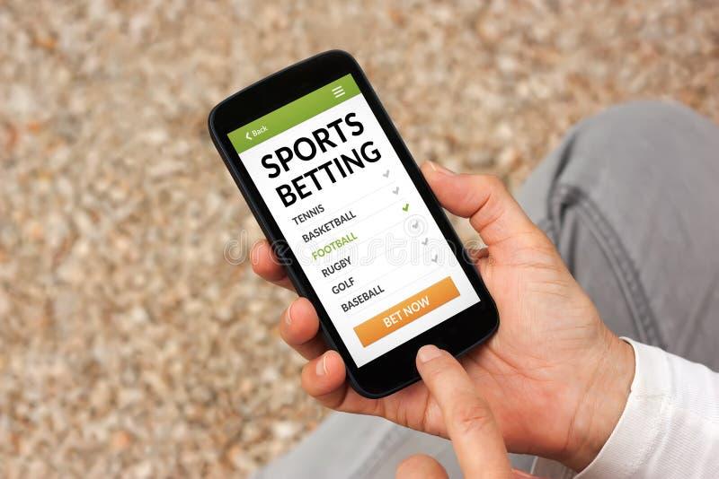 Mains tenant le téléphone intelligent avec des sports pariant le concept sur l'écran photos libres de droits