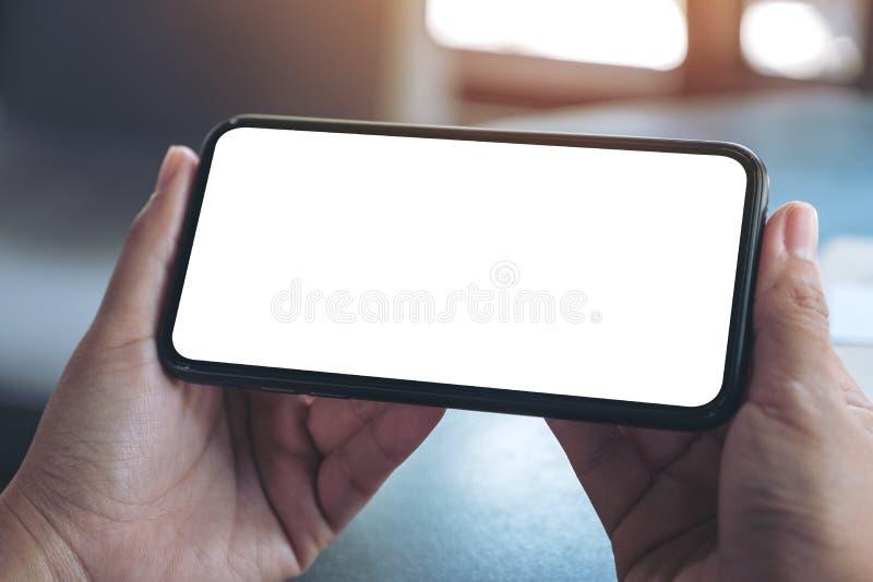 Mains tenant le téléphone portable noir avec l'écran de bureau vide horizontalement image stock