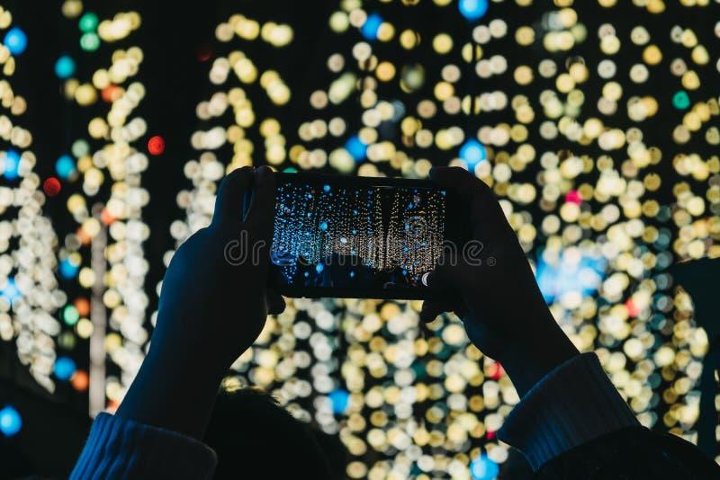 Mains tenant le téléphone portable non identifié au-dessus de la tête, prenant des photos photographie stock