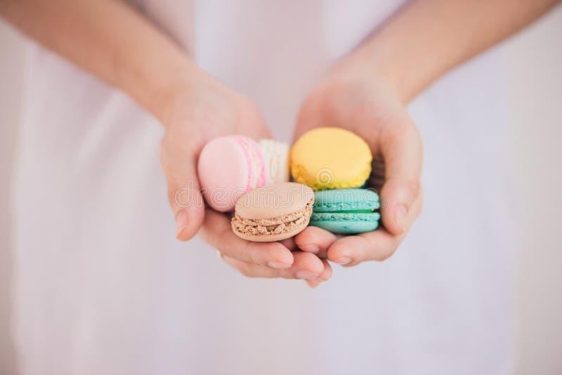 Mains tenant les macarons ou les macarons en pastel colorés de gâteau images stock