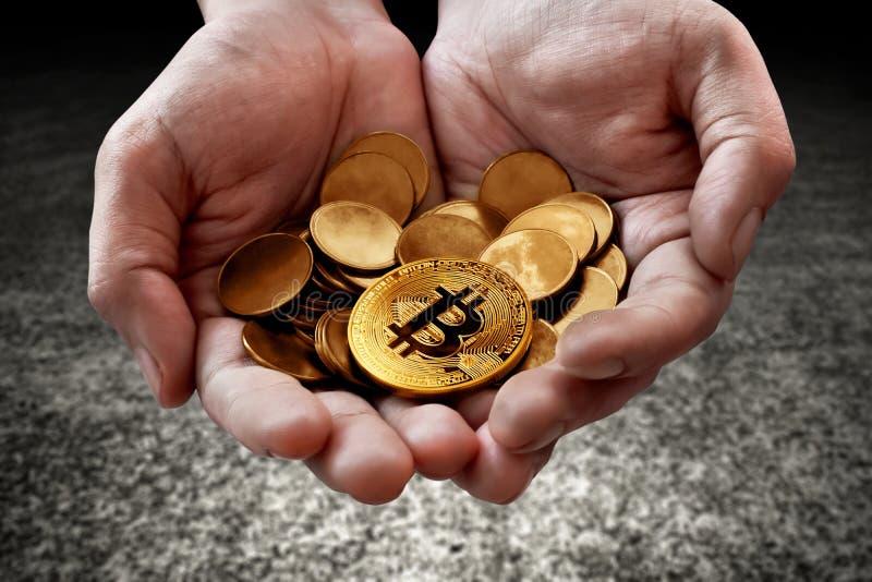Mains tenant les pièces de monnaie d'or de bitcoin images stock