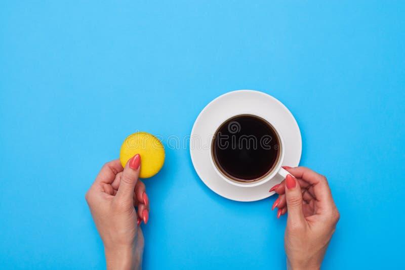 Mains tenant un macaron et une tasse de café photos libres de droits