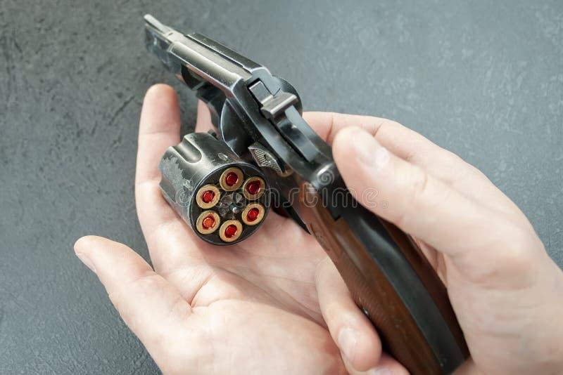 Mains tenant un revolver avec un tambour ouvert avec des cartouches de 9 millimètres images libres de droits