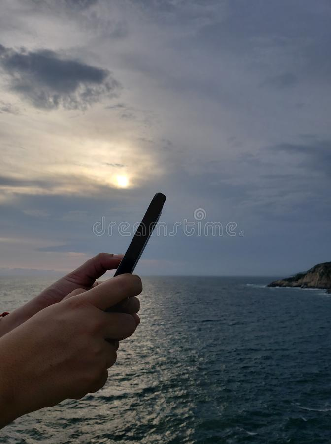 mains tenant un smartphone et un fond avec un paysage tropical photos libres de droits