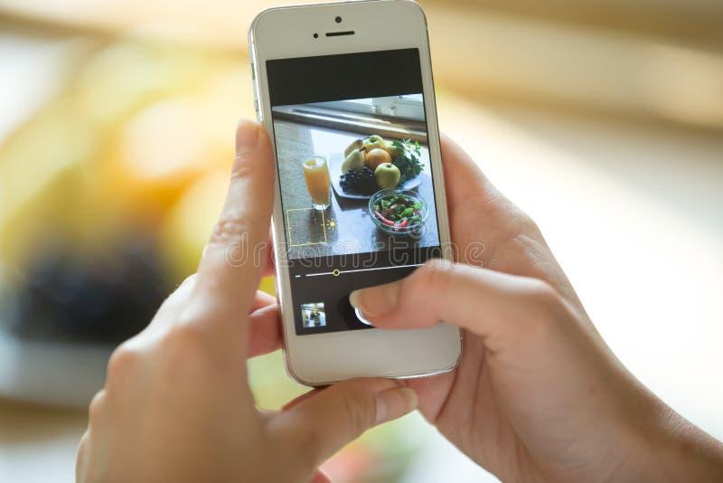 Mains tenant un téléphone avec la photo de nourriture sur l'écran photos libres de droits