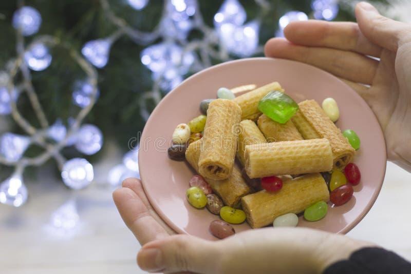 Mains tenant une soucoupe de fête avec des biscuits et des sucreries images libres de droits